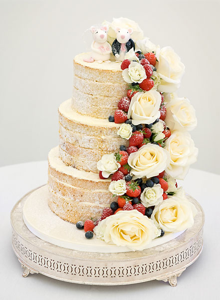 Three Tier Naked Wedding Cake with Layers of Vanilla Buttercream & Strawberry Preserve, with a Cascade of Large Fresh Ivory Roses & Berries. Topped with Bride & Groom Sugar Mice.