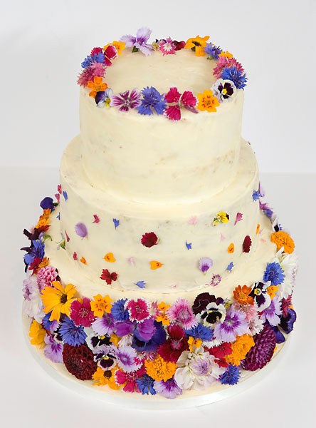 A 'Colour Burst' of Fresh Wild Summer Flowers, covering a Buttercream Iced Wedding Cake, Topped with a Crown.